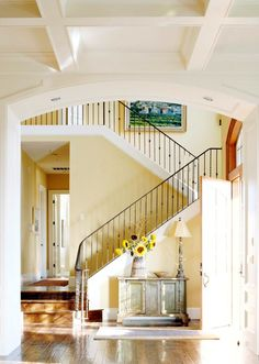 In this home, the soaring entry hall is like the center of a wheel with the other rooms radiating from it. Racing up the staircase like switchbacks, twisted-iron balusters steer the eye upward where the drama unfolds with a gridlike box-beam ceiling in the adjacent great-room.    An aged sideboard fills wall space near the door and creates a place to drop keys.  The wrought-iron banister and a sisal area rug inject texture and convey a French country feeling.  For extra wow, the entry's ceil...