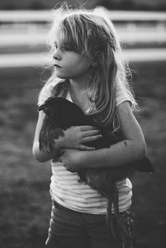 A little country girl holding her favorite chicken.
