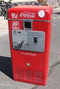 "Vintage Coca-Cola vending machine (""Vendorlator Dual VMC 27A"")."