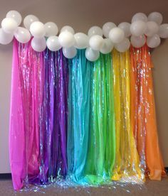 Back drop using plastic table cloths, iridescent door streamers and balloons for clouds
