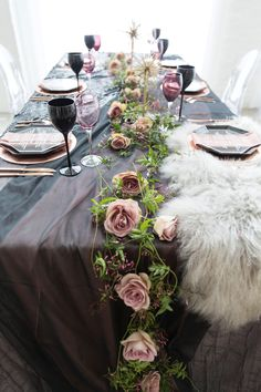 Spring themed wedding reception table decor with dark purple linens, pink rose centerpieces, purple wine glasses, white fur placemats, rose china, rose silverware, and ghost chairs | Chez Chicago Wedding Venues