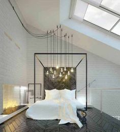 black and white bedroom, multiple lights hung over bed, dark herringbone wood floor, skylight, fireplace