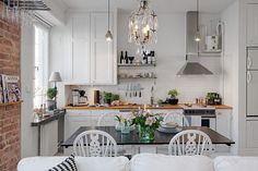 Fehér konyhabútor szép fa munkalappal. étkező fehér székekkel és sötétszürke asztalappal nyitott térben, egyszobás kis lakásban