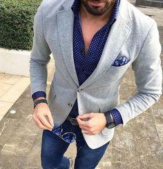 Wear a grey wool coat and navy slim jeans for a work-approved look.   Shop this look on Lookastic: https://lookastic.com/men/looks/blazer-dress-shirt-skinny-jeans/24007   — Navy Polka Dot Dress Shirt  — Navy Paisley Pocket Square  — Grey Wool Blazer  — Navy Bracelet  — Black Watch  — Black Leather Belt  — Navy Skinny Jeans