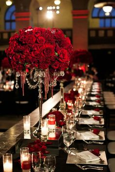 Gorgeous crystal chandelier vases bursting with deep red roses and dahlias. Wedding design by Sterling Engagements.