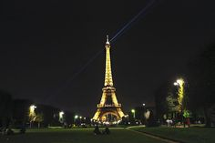Blue Laser Light Beams From Top of Eiffel Tower at Night in Paris, France