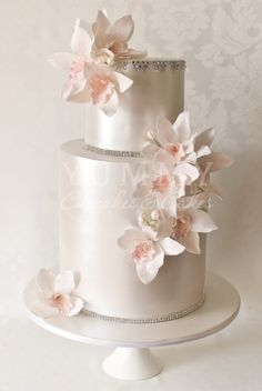 Incredibly elegant wedding cake design with pearlized icing, rhinestones and soft pink orchids. By Yummy Cupcakes & Cakes