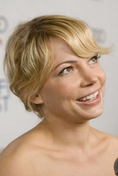 short, wavy, romantic, golden almost looks like an updo but might be her shorter hair.