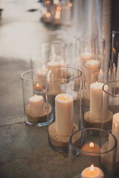 Lots of tall candles in jars of brown rice at a Luce Loft wedding ceremony in downtown San Diego