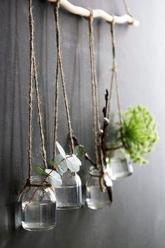 Gebruik een tak om leuke potjes aan op te hangen met plantjes of bloemetjes.