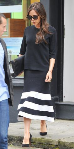 Victoria Beckham modeled her own spring 2015 designs while out shopping in London. She remained true to the classic black-and-white color palette and styled her striped knit flute midi skirt with a black knit, an oversize clutch, and black Monolos.