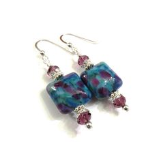 These earrings are made with square blue and purple lampwork beads, purple Swarovski crystals, sterling silver bead caps, small round sterling silver beads and sterling silver spacer beads. They measure approximately 2 inches from the top of the sterling silver earwire.  Click here to see other earrings in my shop: https://www.etsy.com/shop/JewelryDesignsByRita?section_id=14765680