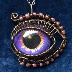 Purple eye pendant. Hand painted cast resin eye, wrapped in copper wire.