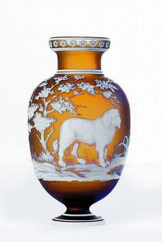 A Thomas Webb & Sons style two colour cameo glass vase of baluster form, the amber glass overlaid with carved scene of a dog by a pond in a landscape, flower head decoration to rim