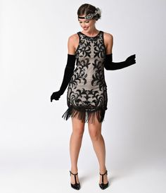 Hello deco! An opulent and flashy flapper frock in a modern silhouette, this vintage style dress is cut in a fitted and soft black beaded mesh tulle over nude knit lining. With scintillating black sequin swirls in a gorgeous jazz age design, offset with s