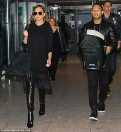 Thigh's the limit: Sexing up her jet-set look, the model, 30, strutted through Heathrow Airport in a pair of vampy black leather thigh-high boots as the family arrived for their flight