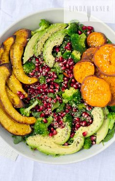 Pretty Holiday Roasted Vegetable Salad is a symphony of sweet potatoes, caramelized acorn squash, rich avocado, crunchy hemp seeds, bright pomegranate, and a great lemony vinaigrette.