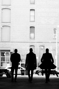 Silhouette of three men from the rear