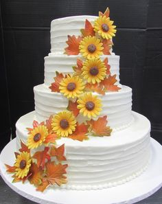 Pretty sunflowers and fall leaves cascading down a tiered cake