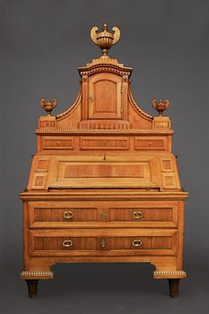 A noble Louis-Seize secretaire  Augsburg, c. 1770/80. Ash tree, massive, partly carved. The bottom with 2 drawers, the blackened writing surface with 4 small drawers inside and framing 4 drawers. The top with 3 drawers and 1 middle compartment and 3 crowning vases. Rest. H. 225 cm, w. 126 cm, d. 69 cm.
