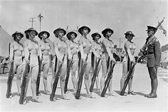 An unidentified corporal from the US Army's 30th Infantry Division (based in the San Francisco Presidio) stands at attention with a group of women in two-piece bathing costumes, doughboy helmets, and heels, each of whom holds an M1917 Enfield rifle, on a parade ground in Camp George Derby, on the grounds of the California Pacific International Exposition in Balboa Park, San Diego California, mid to late 1935. Pin by Paolo Marzioli