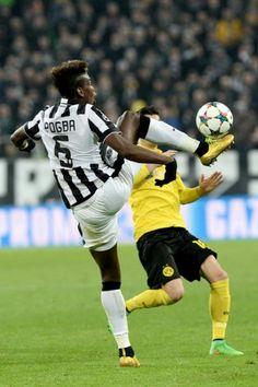 Juventus' Paul Pogba challenges the ball with Borussia Dortmund Sahin Nuri during the Champions League round of 16 first leg soccer match between Juventus and Borussia Dortmund at the Juventus Stadium, in Turin, Italy, Tuesday, Feb. 24, 2015.