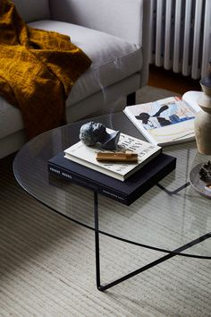 Glass coffee table, incense, light rug, brown blanket. Interior decor trend 2018. Scandinavian decor. Photo: TRNK