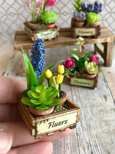 Each of these 1:12 scale garden crates is filled with beautiful flowers and a tiny succulent. The crate has been stained, distressed and labeled. The blossoms are perfectly gorgeous and made of clay, mulberry paper, plastic or tiny beads. A small piece of green burlap is tucked