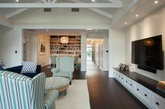 The home's walls are in cream clapboard, which adds a subtle visual detail to the neutral space. The living room is in shades of blue with a large patterned ottoman. On the right wall is a built-in shelving unit with six drawers and a wall-mounted television.