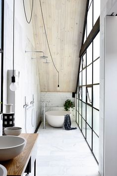 Stunning master bathroom with black framed windows, exposed white bricks, a round bathtub and wooden vanity | Architects EAT