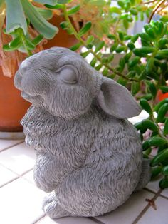 This happy bunny rabbit statue brings a subtle amount of decoration to your outdoor living space. Petite enough to sit inside of a potted plant or window box, she would look just as adorable when placed amongst the flowers of your garden. Cast from durable concrete, he is made to last when placed outdoors but would look just as lovely if kept inside. Would make a wonderful gift for any animal lover! Color options: ~ Unpainted, natural stone (concrete / cement) ~ Multi-tonal gray with p...