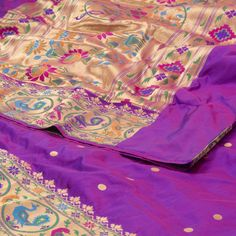 """The """"#Purple"""" #handwoven #Paithani #Silk #Sari from Ghanshyam Sarode is woven with gold zari circular bhutas all over the body that is set off by a gold zari with multicolour peacock and floral motifs on either side. Attractive multicolour floral motifs adorn the gold zari pallu. The border is repeated on the purple blouse that completes the sari."""