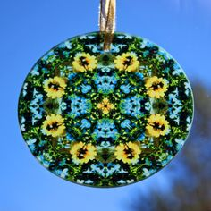 Glass suncatcher adorned with my dragonfly on a yellow daisy boho chic mandala new age sacred geometry kaleidoscope design tilted Jubilant Harmony <br /> <br />This stunning dragonfly glass suncatcher illuminates my geometric mandala kaleidoscope design when light shines through it! It is 3 - ½ inches in diameter and has a beveled edge. The suncatcher comes with...