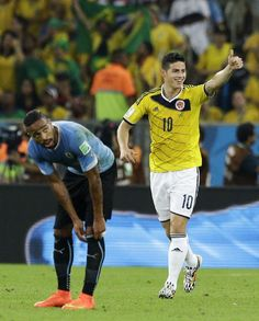 Colombia's James Rodriguez, right, celebrates as he walks past Uruguay's Alvaro Pereira after scoring his side's first goal during the World Cup round of 16 soccer match between Colombia and Uruguay at the Maracana Stadium in Rio de Janeiro, Brazil, Saturday, June 28, 2014
