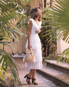 """""""… the perfect dress for a holiday getaway this summer! How dreamy is it?!"""" @thestylebungalow in the Pleated Midi Dress with a fitted waist, ruffle collar detail and pleated tiers. The dreamiest. Watch our Story for more from Stephanie. #itsbanana"""