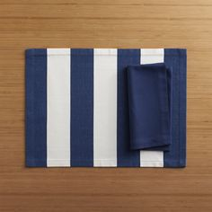 """Broad bands of navy and ivory stretch horizontally across modern, sophisticated hand-dyed cotton placemat.  Elegant yet easy-care napkin is tailor finished with 1"""" hem and mitered corners. Handcrafted placemat is 100% cotton100% cotton napkinMachine wash; warm iron as neededDry placemat flatPlacemat is oversized to allow for shrinkageMade in India."""