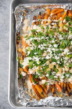 Loaded Greek Sweet Potato Fries! Crispy sweet potato fries with feta, chickpeas, parsley and a lemon-tahini sauce. Vegetarian and gluten-free | www.delishknowledge.com