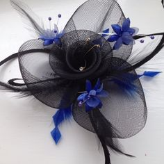 Bought a plain black fascinator for a wedding, but my dress is blue! So I bought some blue craft feathers and blue fabric flowers (with wire stems) from local shops, cut the feathers into diamond shapes and stuck them to the base underneath. Cheered it up a bit Black Fascinator, Blue Crafts, Feather Crafts, Plain Black, Blue Fabric, Stems, Diamond Shapes, Fabric Flowers, Feathers