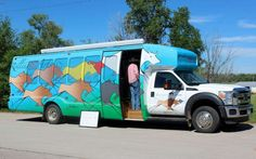 In this June 15, 2016, photo, a bus that has been retrofitted with an art studio and space for a bank teller is seen in the parking lot of a college in Pine Ridge, S.D., to allow people to take a free featherwork classes. The bus is crisscrossing South Dakota's Pine Ridge Indian Reservation to provide emerging artists a space to take and teach arts classes and learn more about the arts business.