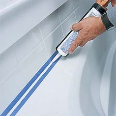 hands using a caulk gun on a tub