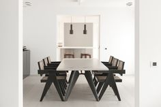 A minimalistic dining space by Nicolas Schuybroek. White walls, white flooring, Pierre Jeanneret chair.