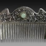 """A silver comb engraved with dragon motifs and set with jade. Different decor on reverse: a vietnamese pictogram with tiny rats among grapes. A similar comb can be seen page 132 in """"The Jewelry of Southeast Asia"""" by Anne Richter, published by Thames & Hudson. It is said that this kind of comb was worn by the middle class women of Southern Vietnam, early-mid- 20th century. Early 20th Century."""