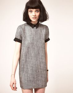 woven shift dress with collar, thick bob and bangs, peachy taupe contouring and no definition on eye