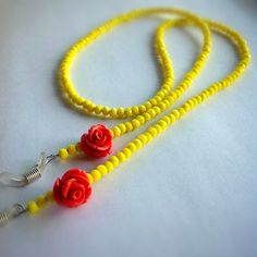 Old-fashioned, but I LOVE these! Luminous eyeglass necklace, a touch of summer for your reading glasses or even for your sunglasses.Yellow glass beads and orange lucite flowers stung on steel wire.Quality eyeglass holder grips.