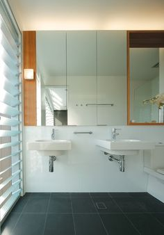 High gloss wall tiles and charcoal floor tiles keep the bathroom clean and minimal., Urbis