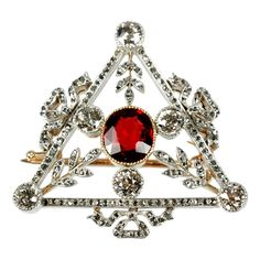 FABERGE Triangular Brooch. A Russian 56 standard gold, diamond and spinel brooch attributed to Faberge (maker's mark partially overstruck by the assay mark), of triangular form; each side adorned with a diamond set bow; the garnet supported by three diamond set, leafy branches and three mine cut diamonds