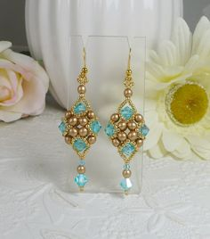 Woven dangle earrings with aqua Swarovski crystals and golden pearls. These elegant hand woven earrings have Swarovski crystals in aqua blue surrounding golden pearls and tons of tiny permanent finish golden seed beads showcasing a Swarovski crystal drop. Attached to hook style style