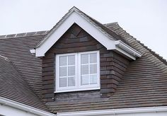 Dormer window: Vertical window protuding through sloping roof. Gable dormer if it has it's own gable or shed dormer if a flat room.