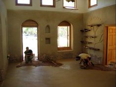 Finishing the earthen floor but notice the shelfs with the mud tree art..Very nice touch....
