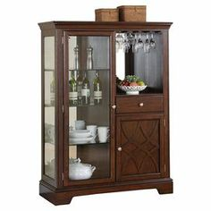 """Bring stately elegance to your dining room, library, or den with this stylish curio cabinet, featuring 3 shelves, 1 drawer, and 1 cabinet.  Product: Display cabinetConstruction Material: Wood, veneers and glassColor: CherryFeatures:  Large surface space for displaying decorative itemsThree interior shelvesOne drawerOne exterior shelfOne cabinet One door Stemware rack  Dimensions: 60"""" H x 44"""" W x 18"""" DCleaning and Care: Wipe with a soft cloth"""